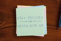 Stay focused and never give up written on note Stock Image
