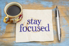 Stay focused reminder or advice on napkin. Stay focused reminder or advice - handwriting  on napkin with cup of coffee against a grunge wood Stock Photo