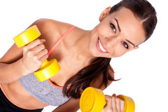 Stay focused on your training. Portrait of a healthy young woman working out with dumbbells and smiling at you Stock Image