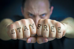 STAY FREE written on an angry man's fists. STAY FREE written on the fingers of an angry man's fists. Message concept image Stock Photo