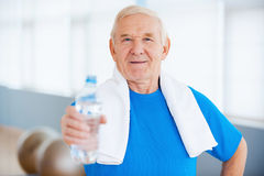 Stay healthy!. Happy senior man with towel on shoulders stretching out a bottle with water while standing in health club Royalty Free Stock Photo