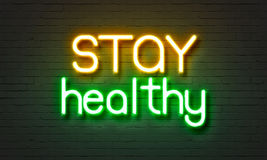 Stay healthy neon sign on brick wall background. Stock Images