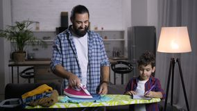 Stay-at-home dad assisting son with schoolwork stock video footage