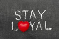 Stay loyal. Phrase handwritten on chalkboard with heart symbol instead of O royalty free stock photo