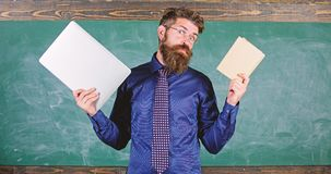 Stay modern with technology. Teacher bearded hipster holds book and laptop. Modern technologies benefit. Digital against. Paper. Choose right teaching method stock photo