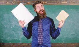 Stay modern with technology. Teacher bearded hipster holds book and laptop. Modern technologies benefit. Teacher. Choosing modern teaching approach. Digital royalty free stock photo