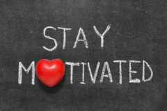 Stay motivated. Phrase handwritten on blackboard with heart symbol instead of O stock photography