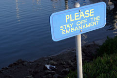 Stay Off the Embankment!. A bird disregards the order to stay off the embankment in the harbor Stock Image
