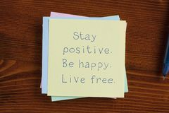 Stay positive Be happy Live free handwritten on note. Top view of Stay positive Be happy Live free written note on the wooden desk Royalty Free Stock Photography