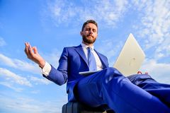 Stay positive reply to client. Work online can be annoying. Communication online full of bullying. Businessman formal. Suit with laptop meditating outdoors stock photography