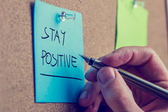 Stay positive. Retro instagram style image of a male hand writing Stay positive on blue post it paper pinned on cork bulletin board royalty free stock images