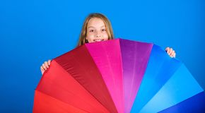 Stay positive though rainy day. Brighten up life. Kid peek out colorful rainbow umbrella. Color your life. Girl cheerful. Hide behind umbrella. Colorful stock image