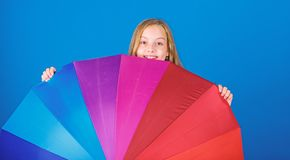 Stay positive though rainy day. Brighten up life. Kid peek out colorful rainbow umbrella. Color your life. Girl cheerful royalty free stock photo