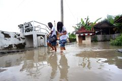 Stay in school during flood. Two high school students crossing the flood for school in the city of Solo, Central Java, Indonesia stock photos