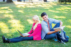 Stay after school. Student girl and boy student hold a laptop an. D looking at the camera while sitting on the grass near the campus of the University at the Stock Photos