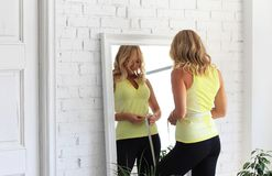 Stay in shape. Young woman with athletic body measures her waist with a measure type in front of a mirror stock photo