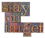 Stay on target. Words in vintage wooden letterpress printing blocks, stained by color inks, isolated on white Royalty Free Stock Photo
