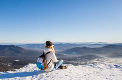 Stay on top. Girl sitting on top of a mountain and looking at the horizon Stock Photography