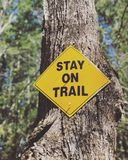 Stay on trail sign. A yellow stay on trail sign on the tree in New England wood Connecticut United States royalty free stock image
