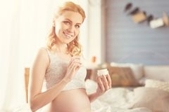 Nice smiling pregnant woman holding beauty product. Stay young and healthy. Cheerful content pregnant woman holding face cream and smiling while expressing Stock Images