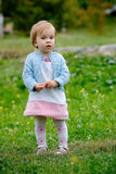 Staying baby girl. A pretty kid girl staying on the meadow and loking into camera royalty free stock photo