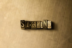 STAYING - close-up of grungy vintage typeset word on metal backdrop Stock Photo