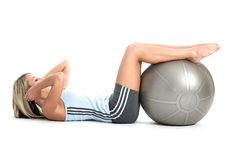 Staying fit. Blond woman in gym outfit excercising with a pilates ball Stock Photography