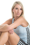 Staying fit 2. Blond woman in gym outfit sitting on the white backdrop Royalty Free Stock Images