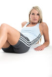 Staying fit 3. Blond woman in gym outfit sitting on the white backdrop Stock Images