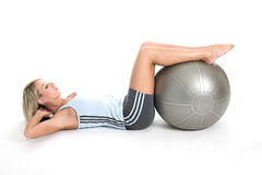 Staying fit 4. Blond woman in gym outfit excercising with a pilates ball Royalty Free Stock Photo