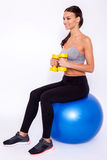 Staying fit. Young beautiful woman in sportswear with perfect body doing exercise with dumbbells and looking away with smile while sitting on fitness balls over Stock Images
