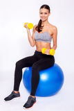 Staying fit. Young beautiful woman in sportswear with perfect body doing exercise with dumbbells and looking at camera with smile while sitting on fitness balls Royalty Free Stock Photography