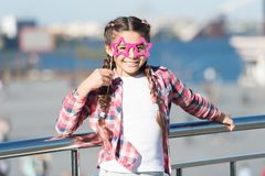 Staying focused with glasses. Small kid smiling with fancy party glasses on urban background. Funny girl holding star. Shaped glasses on stick. Little child stock images