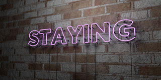 STAYING - Glowing Neon Sign on stonework wall - 3D rendered royalty free stock illustration Stock Photography