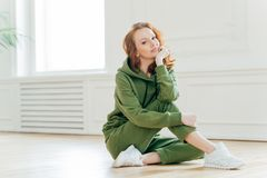 Staying in good shape. Pleasant looking red haired female gymnast with wavy hair, sits on floor in fitness hall, has flexible body. Rests after doing yoga stock image