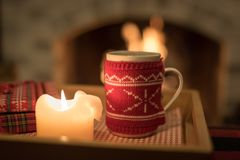Cozy warm drink by the fire. Staying home and snuggling up by the fire with a warm cozy drink and a good book Royalty Free Stock Photo