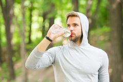 Staying hydrated. Athlete drink water after training in park. care body hydration. sport and health. man in hood drink. Water. refreshing vitamin drink after stock photo