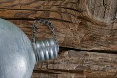 Staying hydrated concept. Full vintage military aluminum canteen, water flask with cap screwed on coarse weathered wood background Royalty Free Stock Image