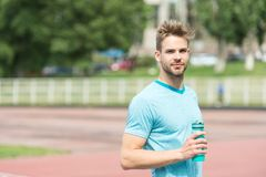 Staying hydrated. Man athletic appearance holds water bottle keep staying hydrated during training. Guy sport clothes. Refreshing. Athlete cares body hydration Stock Image