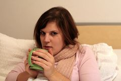 Staying Sick At Home. A woman calling in sick and staying in bed Stock Images