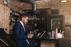 Young man sitting at bar counter and using digital tablet royalty free stock image