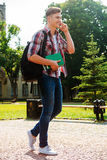 Staying in touch with friends. Full length of handsome male student talking on the mobile phone and smiling while walking outdoors Royalty Free Stock Image