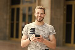 Staying in touch. Send message concept. Man with beard walks with smartphone, urban background. Guy use smartphone to. Send message stay in touch. Man typing stock photo