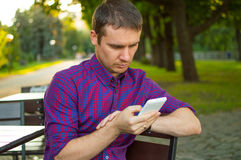 Staying in touch. Young man typing message on his mobile phone Royalty Free Stock Images