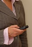 Staying up to date with mobile. Woman holding a phone, while typing a text message Stock Image