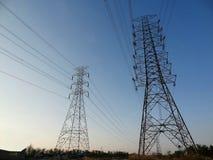 Stazione ad alta tensione della torre del pilone del palo di elettricità contro cielo blu Fotografie Stock Libere da Diritti