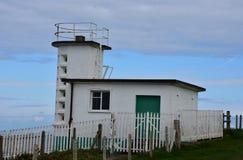 Stazione bianca della guardia costiera del mattone situata sulle scogliere del mare fotografia stock