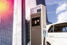 Stazione di carico per le e-automobili con la facciata di un grattacielo fotografia stock libera da diritti