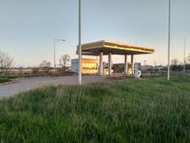 Stazione di servizio abbandonata all'alta erba verde di tramonto Immagine Stock Libera da Diritti
