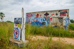 Stazione di servizio abbandonata ed invasa con i graffiti variopinti ed il cielo drammatico Immagine Stock
